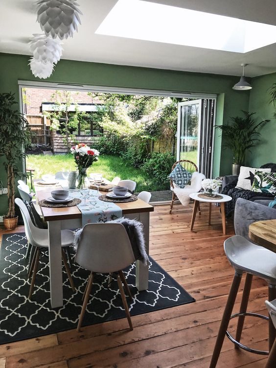 dining room, wooden floor, green wall, black rug, wooden dining table, white midcentury modern chairs, white ceiling, grey sofa, white round table, glass ceiling window