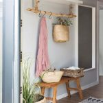 Entryway, Wooden Floor, Grey Wall, Wooden Bench, Wooden Rod, White Floating Shelves, White Patterned Rug, Rattan Basket