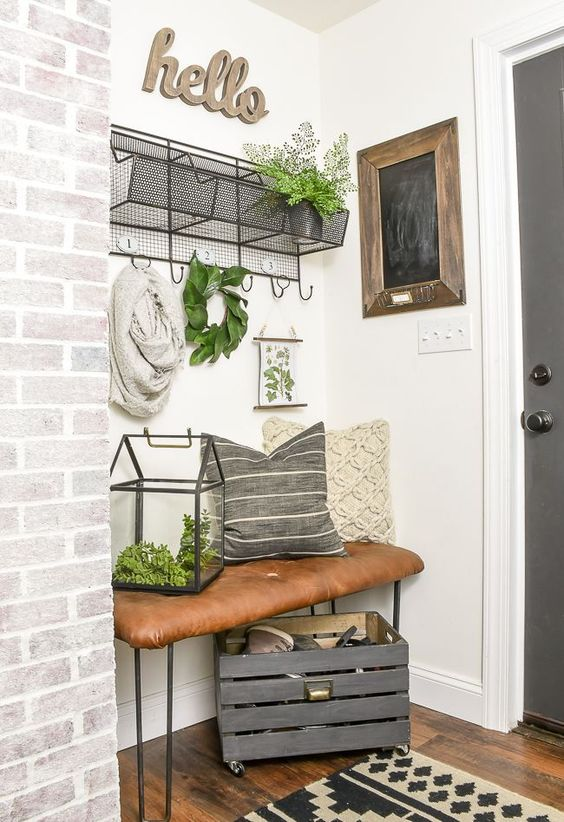entryway, wooden floor, white wall, metal bench with brown leather cushion, black metal shelves, patterned rug