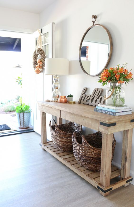 entryway, wooden floor, wooden console table, round mirror, white wall, white table lamp, rattan basket