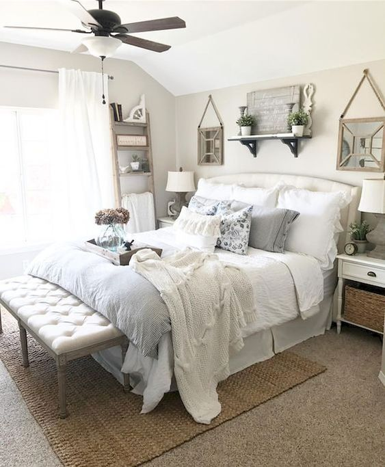 farmhouse bedroom, brown rug, bench with tufted seat, cream wall, ceiling fan and lamp, white bed platform, white side table
