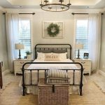 Farmhouse Bedroom, Brown Rug, Rattan Rug, Grey Wall, Indented Tray Ceiling, Chandelier, Black Metal Bed Platform, White Side Cabinet, White Table Lamp