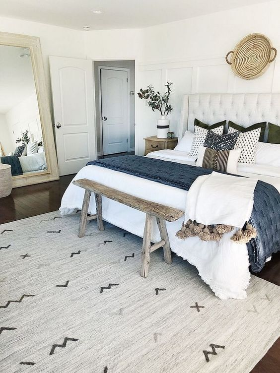 farmhouse bedroom, dark wooden floor, white wall, white tufted headboard, wooden bench, tall mirror
