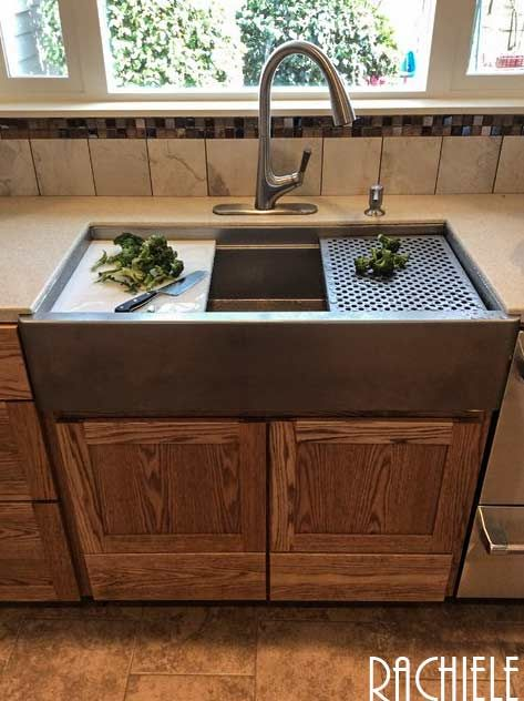 gey sink, wooden cabinet, brown counter top, cream backsplash, stainless faucet