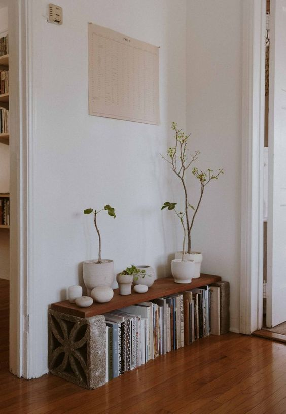 hallway, wooden floor, low shelevs, plants in white pots, white wall