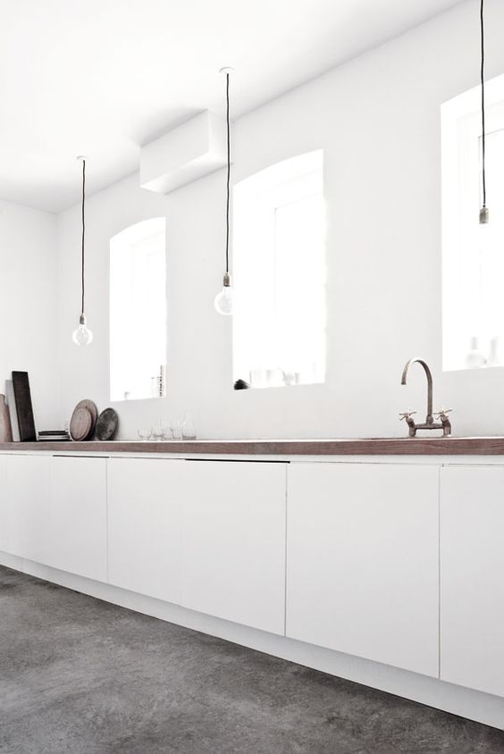 kiche, grey floor, white wall, white cabinet, clear bulb pendants, wooden counter top