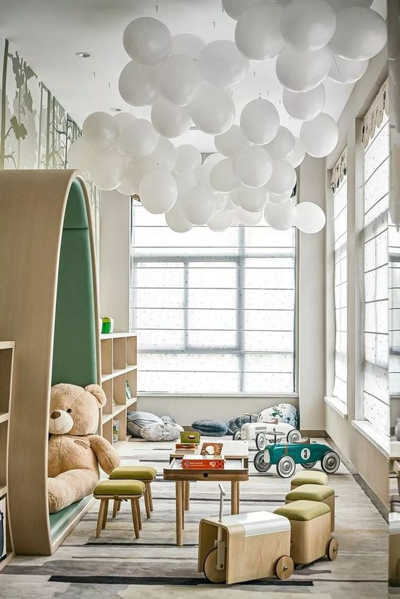 kids room, floor rug, white ceiling, white baloon, low table, low stools, wooden shelves, windwos