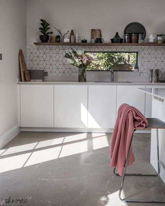 kitchen, concrete floor, white wall, white bottom cabinet, hexagonal backsplash, white island, floating wooden shelves