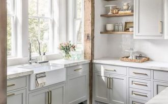 kitchen, dark wooden floor, white wall tiles, white cabinet, wooden floating shelves, white marble counter top, white apron sink, wooden beam frame, white frame windows,