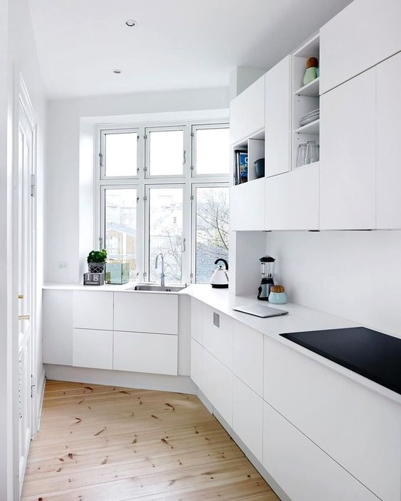 kitchen, long galley, wooden floor, white bottom cabinet, white wall, white upper cabinet