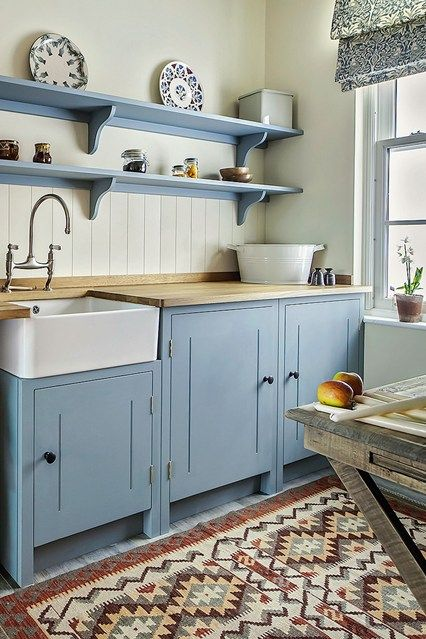 kitchen, patterned rug, white wooden backsplash, wooden counter top, white apron sink, blue floating shelves