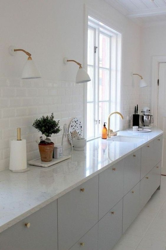 kitchen, white floor, white subway wall tiles, white counter top, off white bottom cabinet, white sconces.