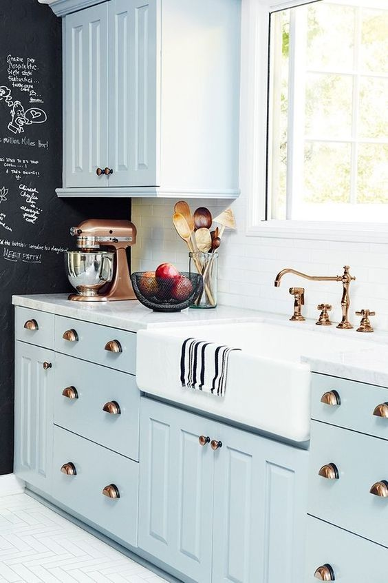 kitchen, white wooden floor, black wall, white backsplash, blue cabinet, white marble counter top, white apron sink