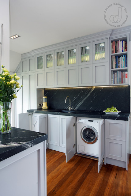 kitchen, wooden floor, black marble backsplash and counter top, grey cabinet, white laundry machines