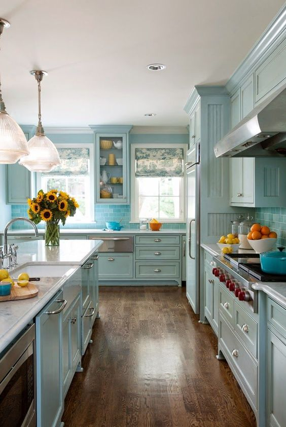 kitchen, wooden floor, blue wooden cabinet, white ceiling, blue island with white counter top, blue pendant