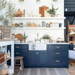 Kitchen, Wooden Floor, Dark Blue Bottom Cabinet, White Shiplap Wall, White Counter Top, White Apron Sink, White Shelves, Golden Sconces