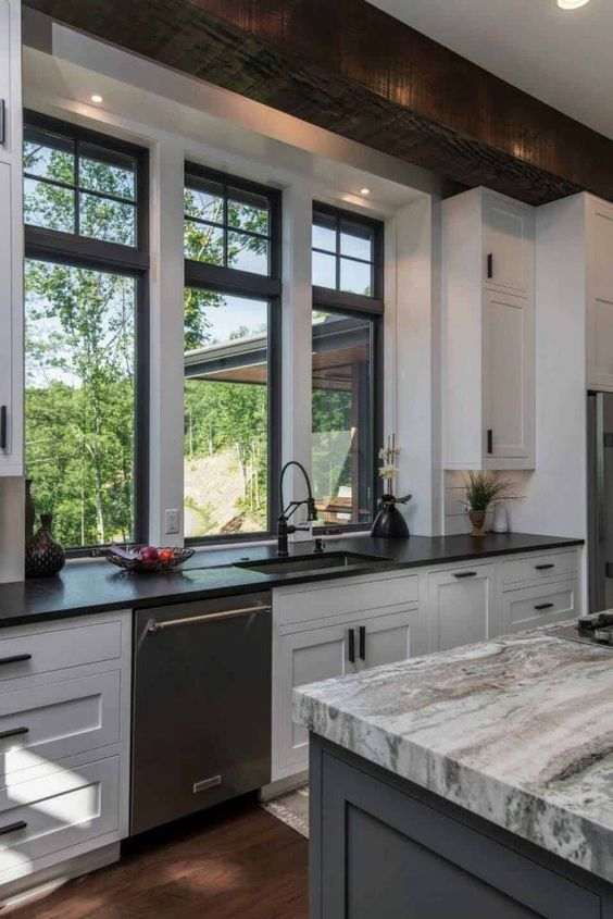 kitchen, wooden floor, white bottom cabinet, black counter top, grey island, grey marble top, white wall, glass