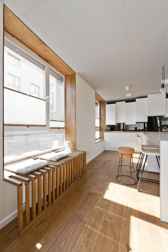 kitchen, wooden floor, white cabinet, black wall, white island, wooden grid window seat