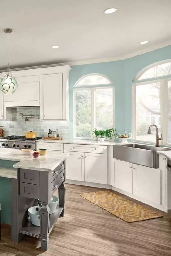 kitchen, wooden floor, white ceiling, white bottom cabinet, white upper cabinet, blue island with white marble top,
