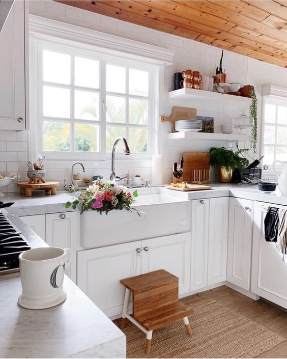 kitchen, wooden floor, white wall, white bottom cabinet, white apron sink, wooden stepping stool, white framed glass window