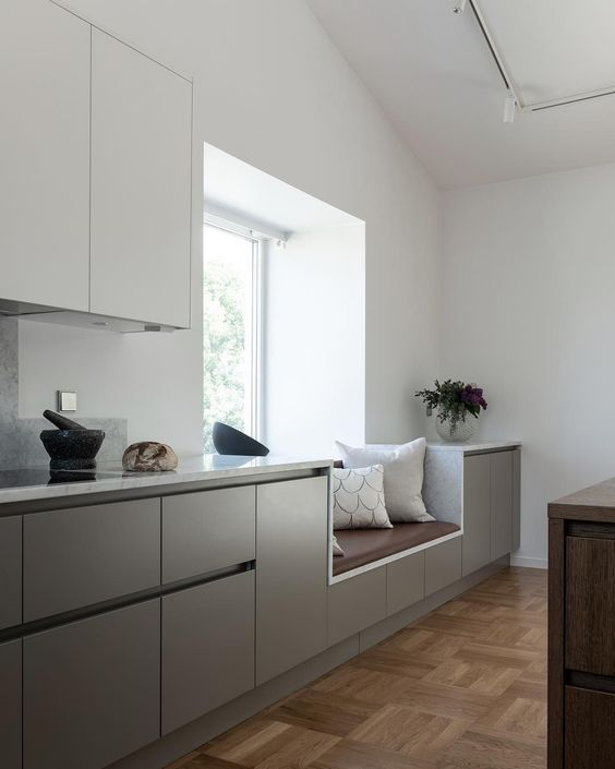 kitchen, wooden floor, white wall, white upper cabinet, light grey bottom cabint, brown leather,