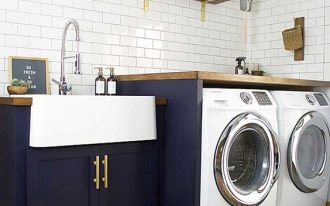 laundry room, black cabinet, white apron sink, white machines, white subway wall tiles, floating shelves, grey floor, patterned rug