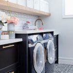 Laundry Room, Black Machines, Black Bottom Cabinet, Golden Handle, White Counter Top, White Wall, White Subway Backsplash, Patterned Floor