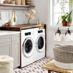 Laundry Room, Pink Black Patterned Floor Tiles, White Wall, White Machines, Wooden Box, Grey Cabinet, White Counter, Wooden Floating Shelves, Rattan Bench