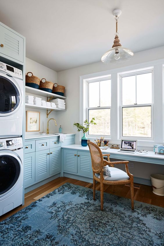 laundry room, wooden floor, white wall, blue cabinet with white counter top, wooden rattan chair, flower pendant, laundry machines, window