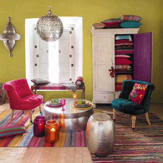 living room, brick floor, green wall, moroccan pendant, silver ottoman, silver coffee table, dark green chair, white cupboard, white window, colorful striped rug