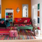 Living Room, Brick Floor, Orange Wall, Moroccan Pendant, Pink Sofa, Green Chair, Green Wooden Coffee Table, Pink Ottoman, Striped Colorful Rufg White Wall
