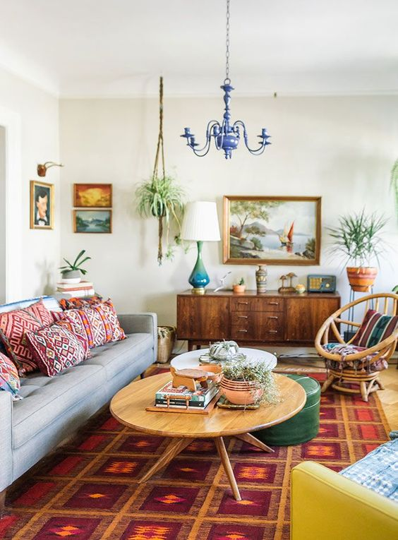 living room, brown floor, red rug, white wall, blue chandelier, blue sofa, round wooden coffee table, yellow chair, rattan chair