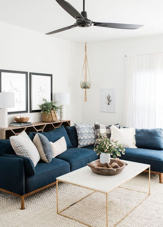 living room, brown rug, white wall, white coffee table, blue corner sofa, black ceiling fan