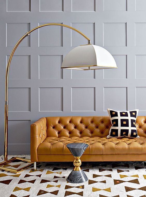 living room, cream brown yellow rug, grey marble side table, grey wall, golden floor lamp with white cover, orange leather sofa