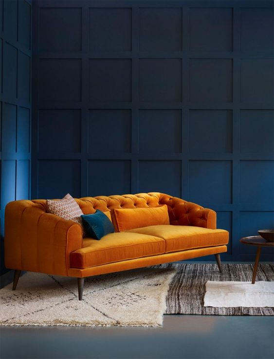 living room, dark blue wall, grey seamless floor, rugs, orange sofa,