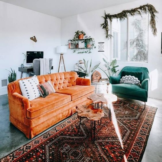 living room, gey concrete floor, white wall, orange velvet sofa, green velvet chair, patterned rug, wooden coffee table, study table, floating shelves, white floor lamp