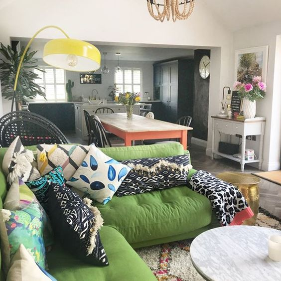 living room, green plush sofa, white marble round coffee table, pink floor lamp, open kitchen and dining
