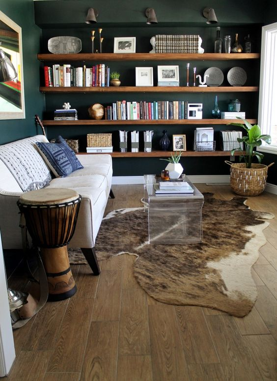 living room, ooden floor, white sofa, wooden floating shelves, dark green wall, acrylic coffee table