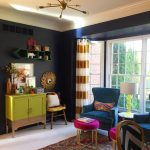 Living Room, White Floor, Black Wall, Patterned Rug, Blue Chairs, Pink Ottoman, Green Cabinet, Modern Pendant