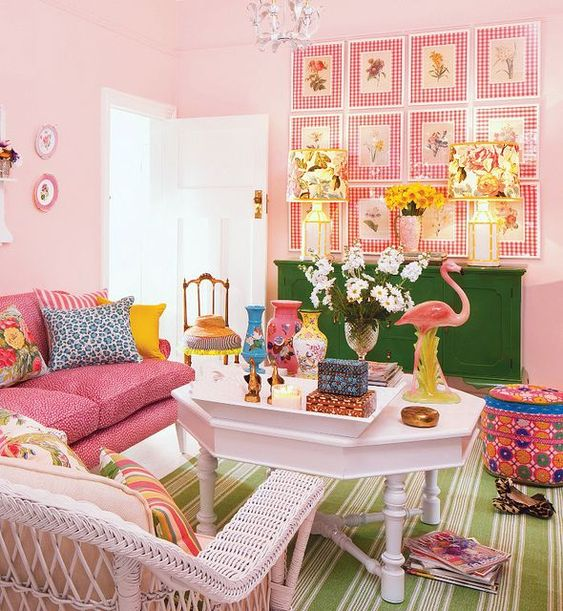 living room, white floor, green rug, white geometrical coffee table, pink sofa, white rattan chair, pink wall, green cabinet