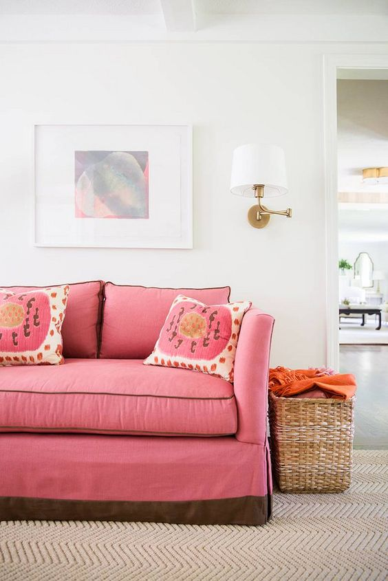 living room, white wall, brown rug, pink sofa, rattan basket, white sconce, white framed painting, white wooden beam