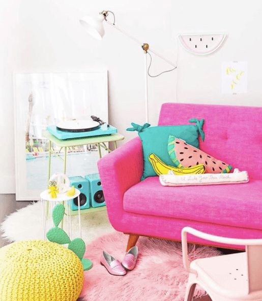 living room, white wall, pink sofa, green side table, pink rug, yellow knitted ottoman, pink chair, white floor lamp