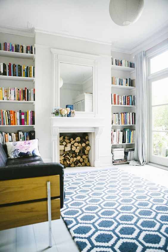 living room, white wooden floor, white wall, white ceiling, white built in shelves besides fire place, white framed mirror, black leather sofa, blue patterned rug