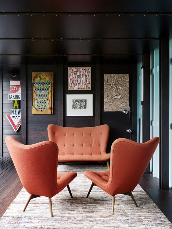 living room, wooden floor, dark wooden wall, orange sofa, orange chairs, rug