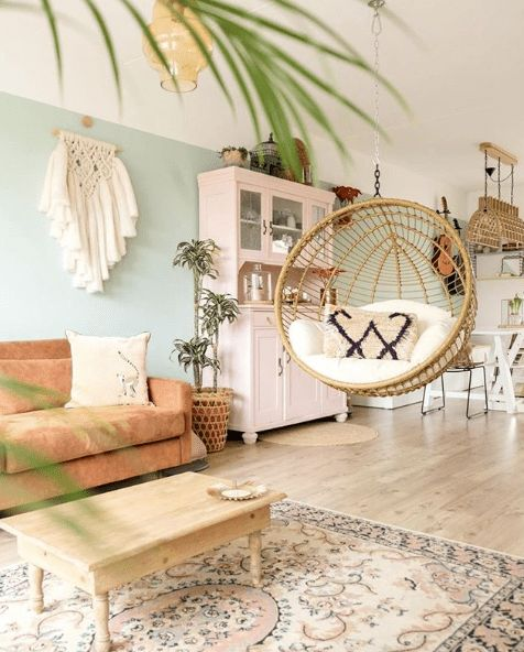 living room, wooden floor, white ceiling, mint green wall, brown patterned rug, wooden coffee table, brown sorfa rattan round swing, pink cabinet