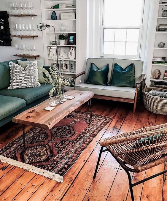 living room, wooden floor, white wall, green sofa, wooden sofa with light green cushion, wooden coffee table, rattan chair, white shelves