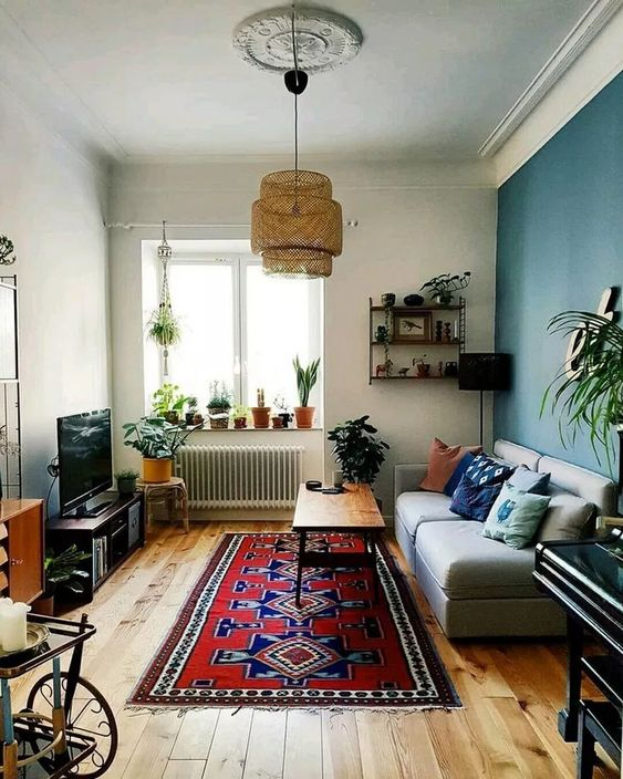 living room, wooden floor, white wall, green wall, red blue patterned rug, wooden coffee table, rattan pendant, light blue sofa