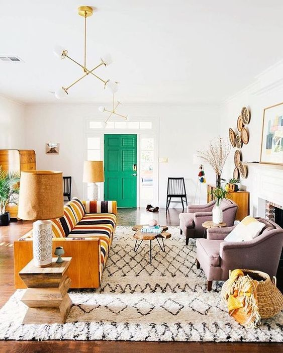 living room, wooden floor, white wall, light purple chairs, striped warm sofa, green door, wooden coffee table