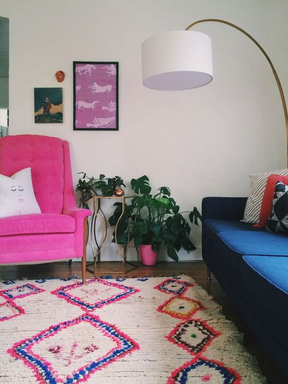 living room, wooden floor, white wall, pink chair, blue sofa, white floor lamp, white rug with pink blue accent