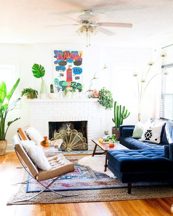living room, wooden floor, white wall, white subway fireplace, blue tufted sofa, wooden coffee table, brown chairs, ceiling fan